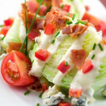 classic wedge salad with iceberg lettuce, blue cheese dressing, bacon, and tomato