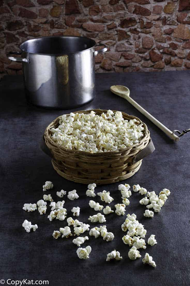 a basket of kettle corn with a stainless steel pot behind it
