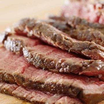 Slices of cooked beef tenderloin on a cutting board.