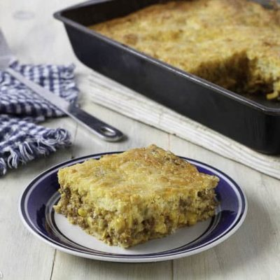 Slice of Mexican Cornbread Casserole on a plate in front of a pan of the casserole.