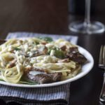 Steak on top of a bed of alfredo sauce and pasta.