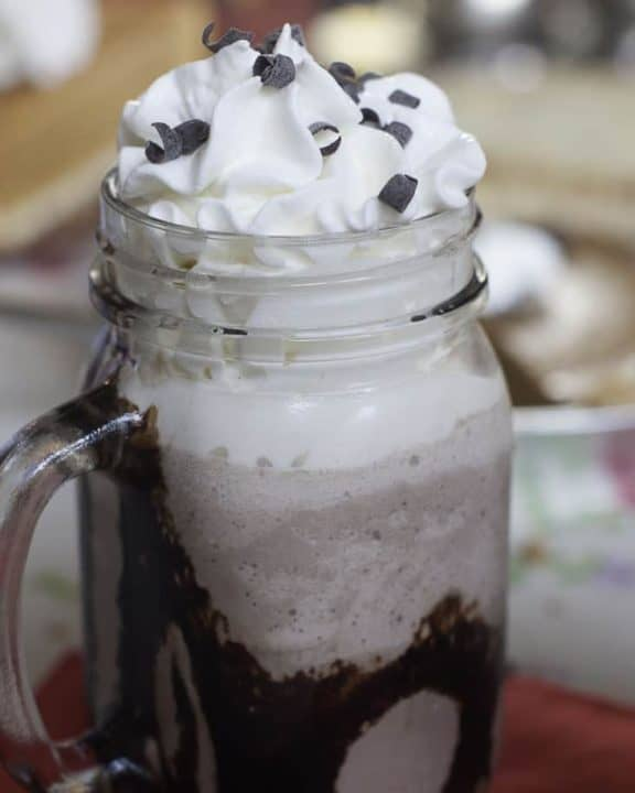 a glass of frozen hot chocolate topped with whipped cream and chocolate shavings