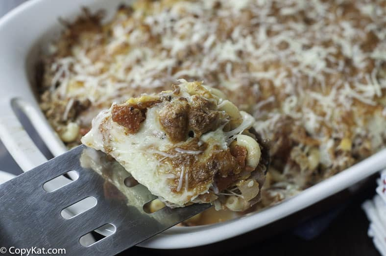 ground beef and macaroni casserole on a spatula and in a baking dish