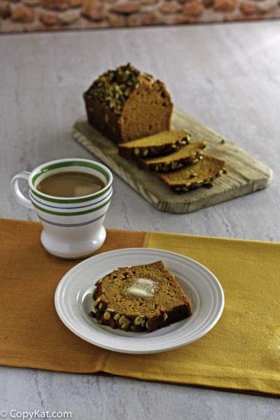 A slice of homemade copycat Starbucks Pumpkin Bread on a plate in front of a cup of coffee and a loaf on a bread board.
