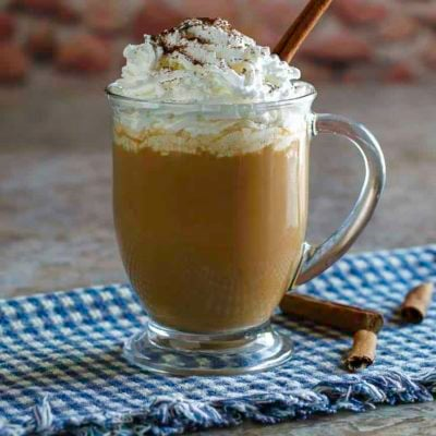 Homemade copycat Starbucks Pumpkin Spice Latte with whipped cream in a clear coffee mug.