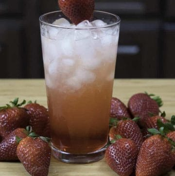 a glass of homemade Sonic strawberry lemonade and fresh strawberries