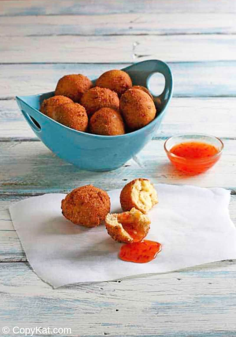A bowl hush puppies with chili sauce
