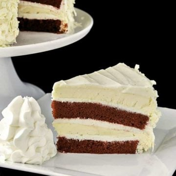 a slice of homemade Cheesecake Factory Red Velvet Cheesecake beside the cheesecake on a stand.