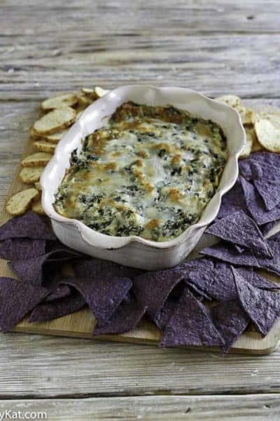 Homemade Olive Garden Artichoke Spinach Dip in a serving dish with crostini and tortilla chips around it.