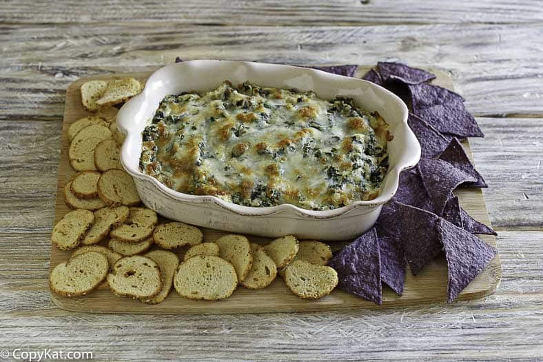 Homemade Olive Garden Artichoke Spinach Dip, crostini, and tortilla chips on a wood platter.
