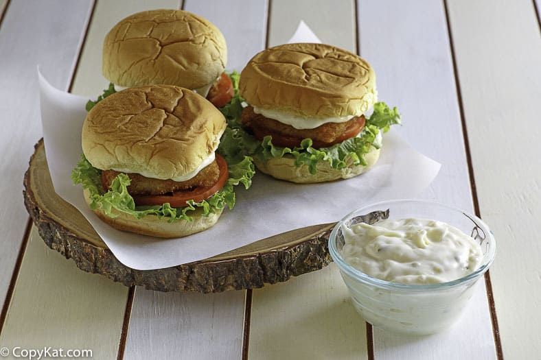 Homemade McDonald's Tartar sauce in a small bowl next to 3 fish filet sandwiches.