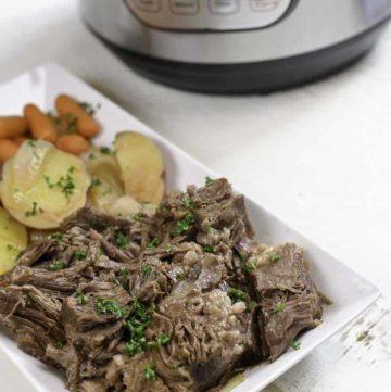 Pot roast on a platter next to an Instant Pot