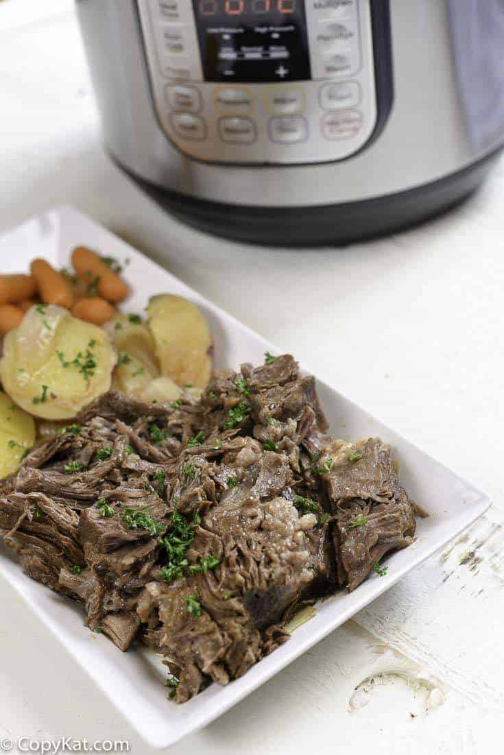 Pot roast on a platter next to an Instant Pot