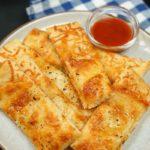 homemade cheese breadsticks and marinara sauce on a plate