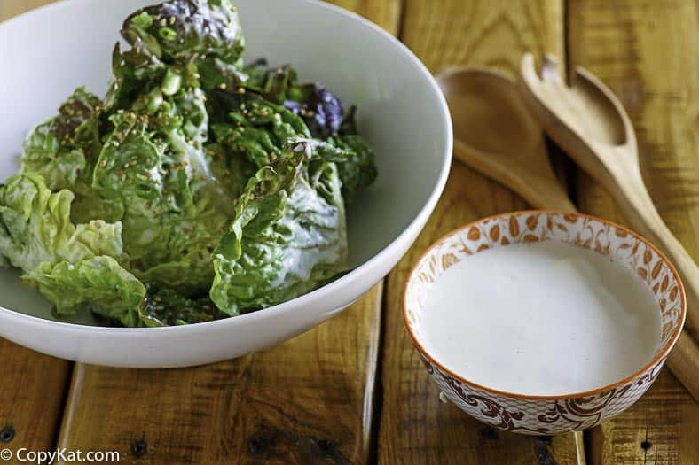 Homemade creamy Japanese Salad Dressing in a small bowl next to lettuce in a white bowl.