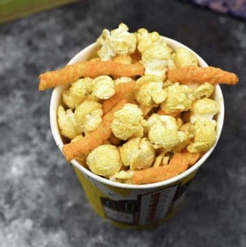 Homemade Cheetos Popcorn in a paper popcorn cup.