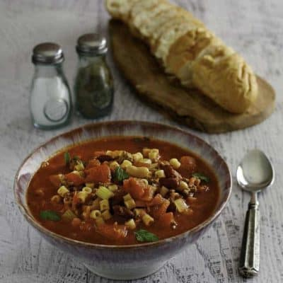 A bowl of homemade Olive Garden Pasta E Fagioli soup and a loaf of bread.