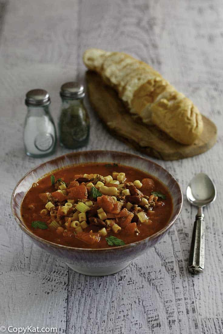 A bowl of homemade Olive Garden Pasta E Fagioli soup and loaf of bread.
