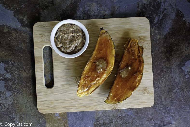 Homemade copycat Outback Steakhouse Baked Sweet Potato on a wood cutting board.