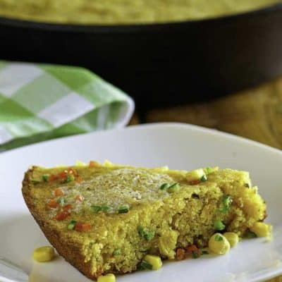 a plate with a slice of jalapeno cornbread with melted butter on top.