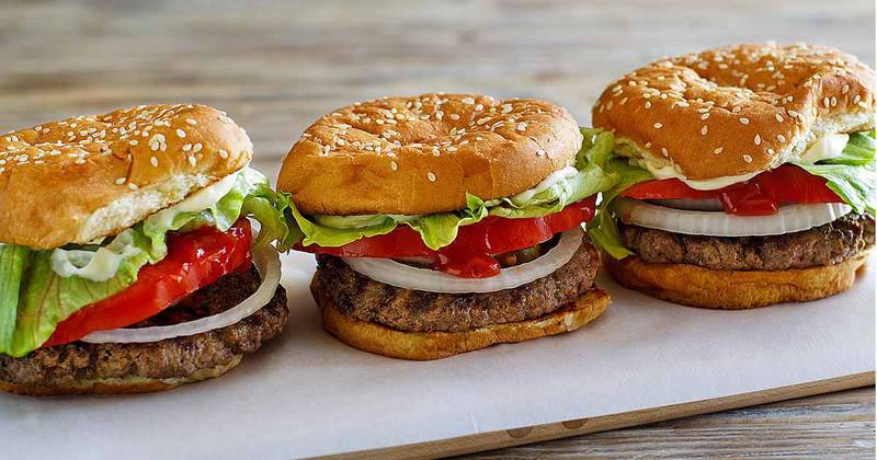 three homemade Burger King Whopper burgers on parchment paper