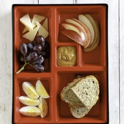 Slices of eggs, cheese, apples, and bread in a red bento box.