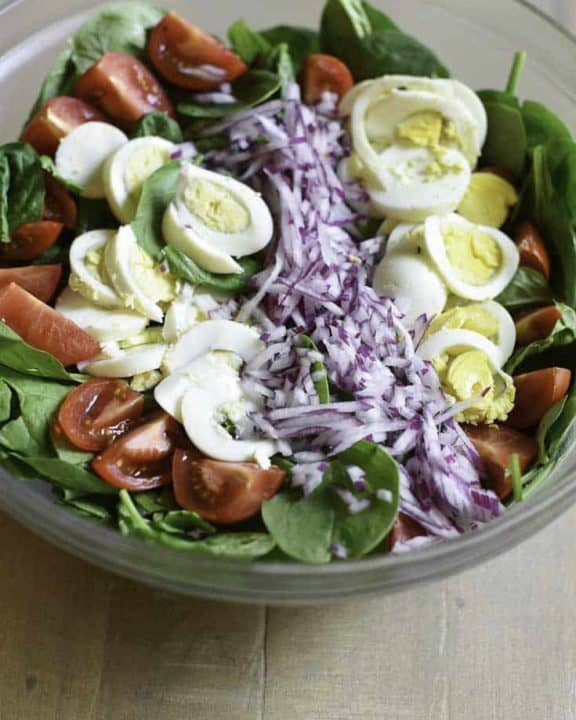 a bowl of spinach salad with hot bacon dressing