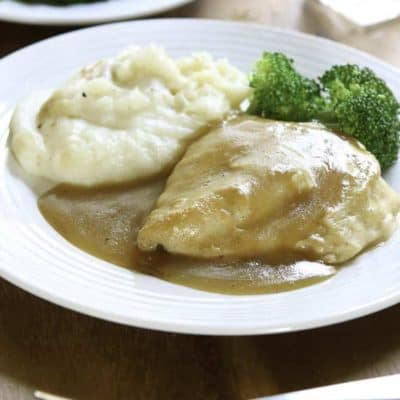 chicken covered in gravy, mashed potatoes, and broccoli on a plate