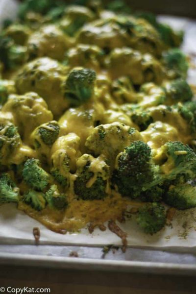 Oven roasted broccoli and cheddar cheese on a baking sheet.