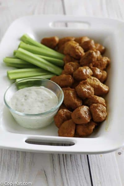 Boneless Buffalo Chicken Bites on a platter with blue cheese dressing and celery sticks