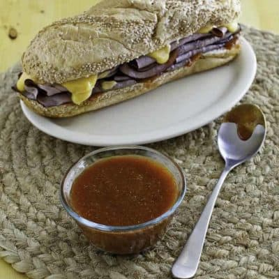 Homemade Arbys sauce beside a roast beef sandwich