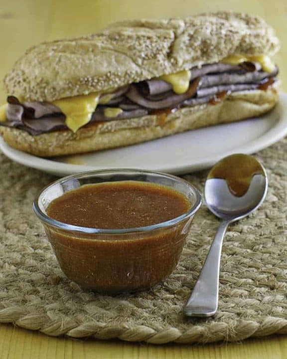 A bowl of homemade Arbys sauce and roast beef sandwich.
