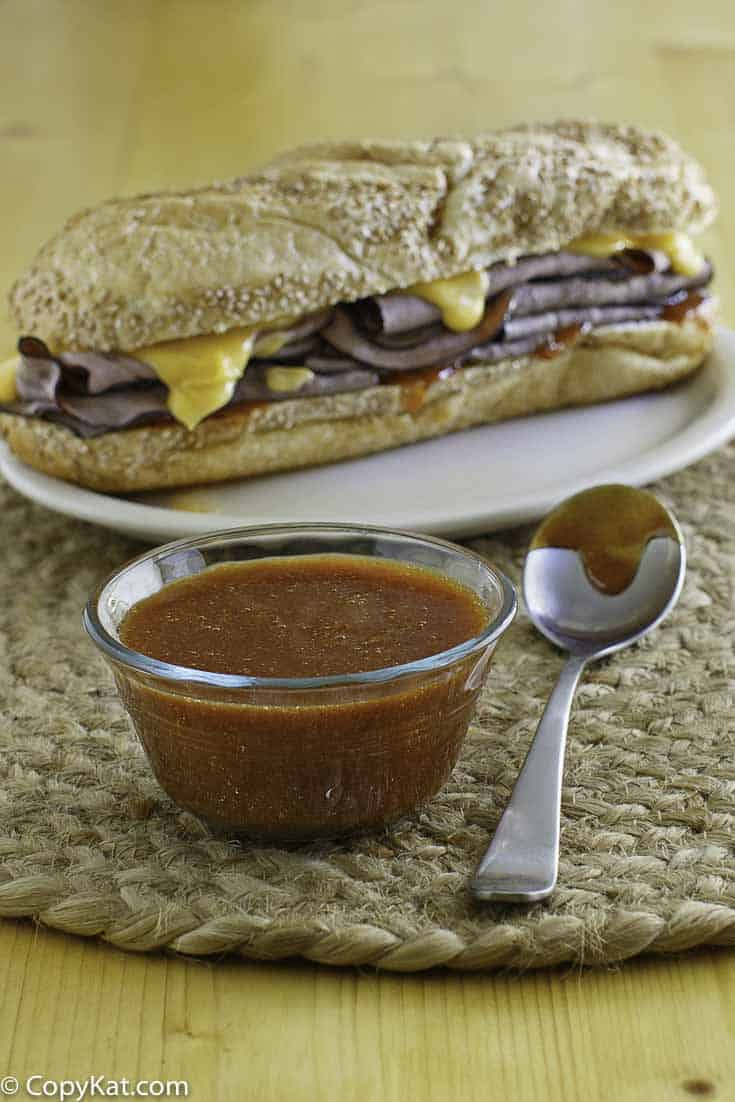 A bowl of homemade Arbys sauce in front of a roast beef sandwich