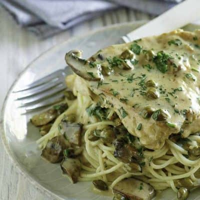 Homemade copycat Cheesecake Factory Chicken Piccata and pasta on a light blue plate.