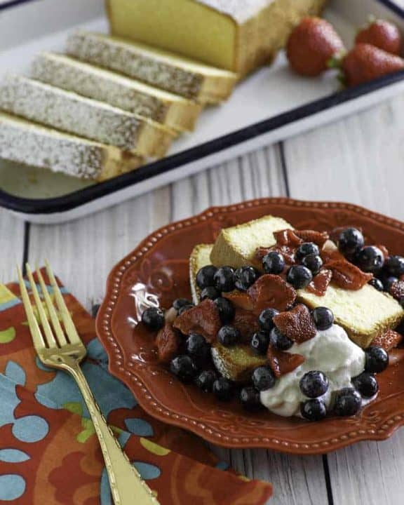 Homemade copycat Sara Lee Pound Cake with fruit in front of the cake on a platter.