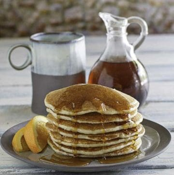 a stack of country griddle cakes with syrup