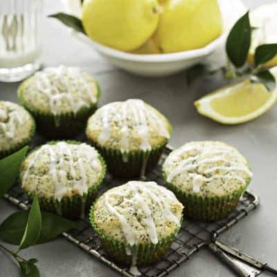 six bakery style lemon poppy seed muffins and lemons
