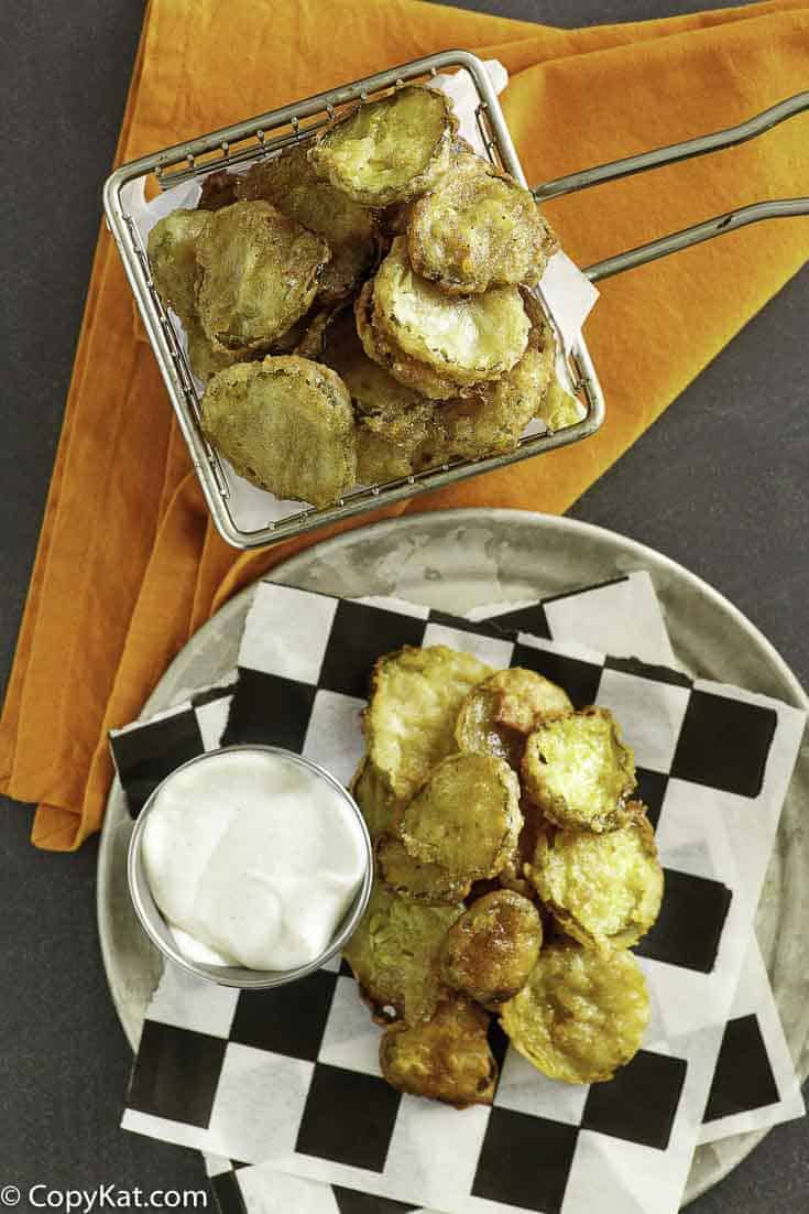 fried pickles in a fry basket and on a plate