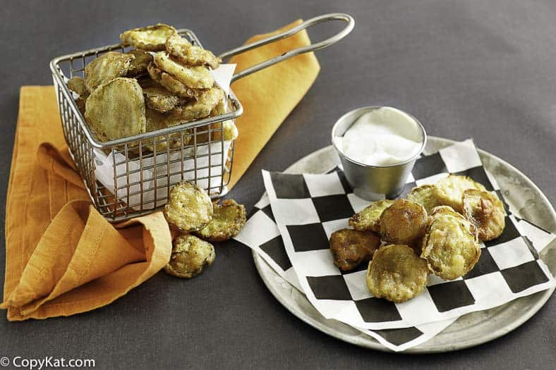 fried pickles in a fryer basket and on a plate