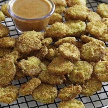 Homemade copycat Red Robin Pickle Nickels (fried pickles) and dipping sauce on a serving platter.