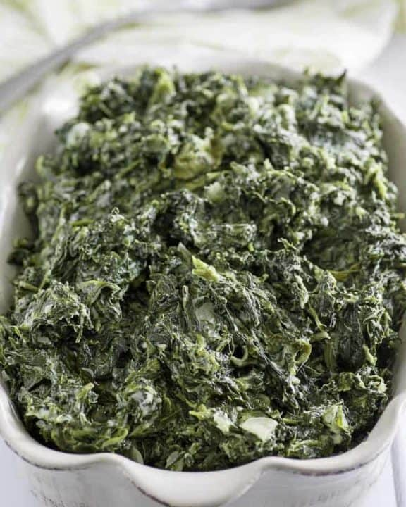 Homemade copycat Boston Market creamed spinach in a white serving dish.