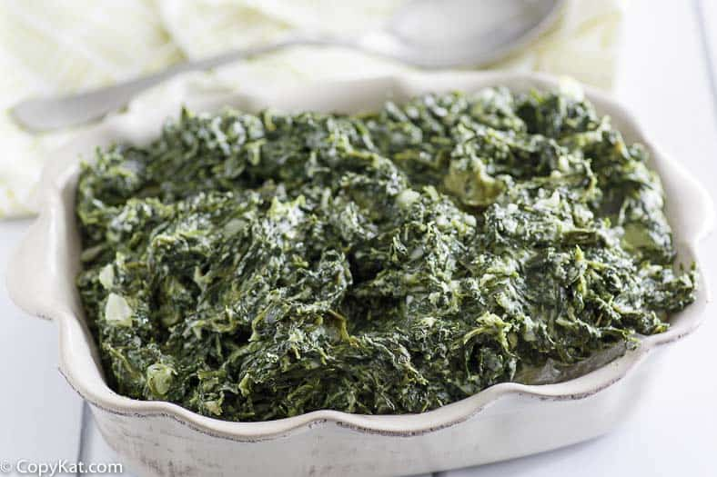 Copycat Boston Market Creamed Spinach in a scalloped edge serving dish.