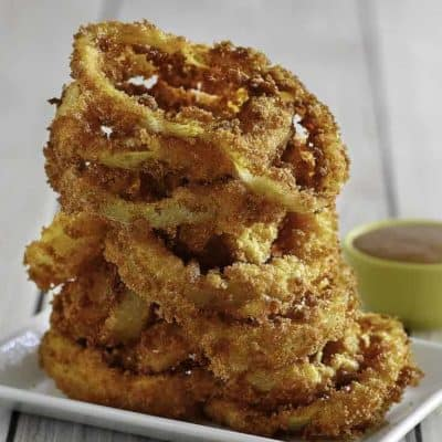 Homemade copycat Red Robin Onion Rings stacked on a white plate.