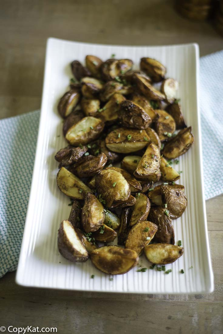 A serving dish of roasted red potatoes.