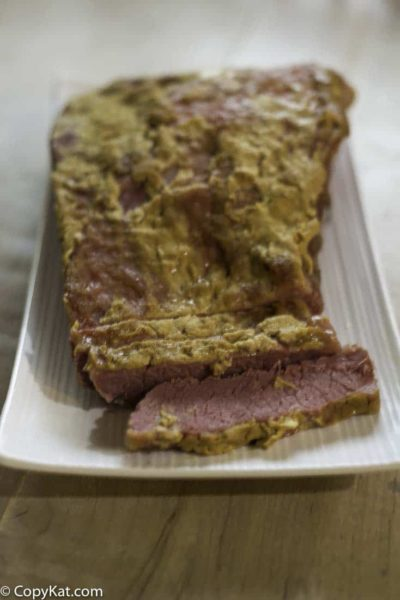 Corned Beef baked with Dijon Mustard and brown sugar on a plate.