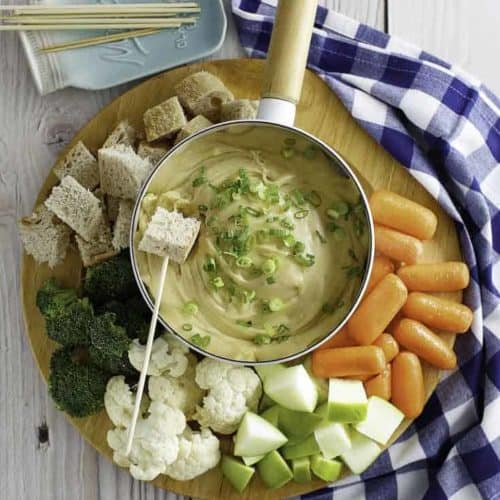 Cheese fondue pictured with bread cubes, carrots, cauliflower, and more.