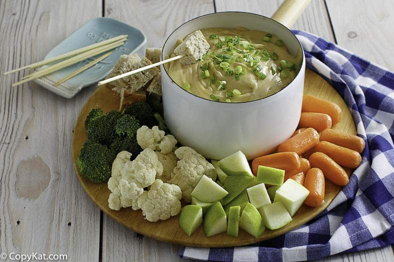 Three cheese fondue in a pot served with fruit, vegetables, and bread.
