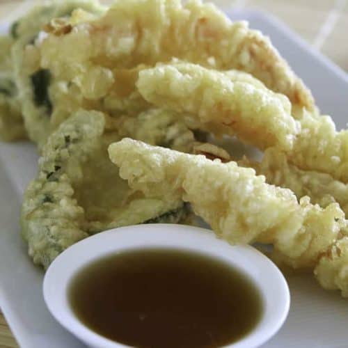 Vegetables fried in tempura batter on a plate.