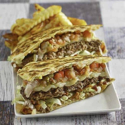 A quesadilla cheeseburger cut in half on a plate with french fries
