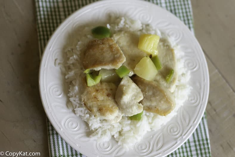 A plate of baked sweet and sour chicken, pineapple, green bell peppers on a bed of rice.